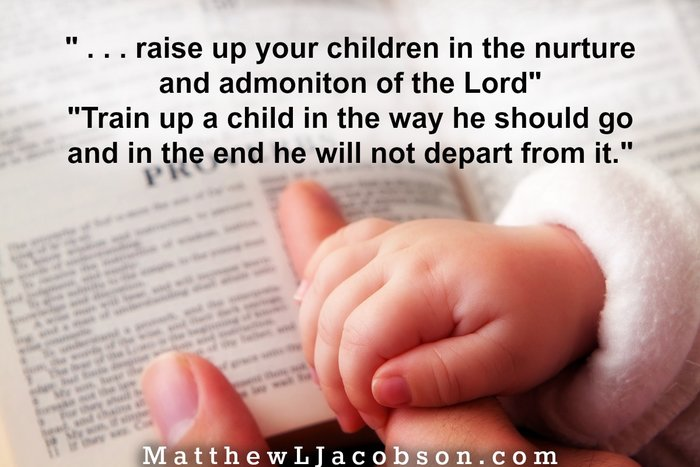 Baby holding father's finger as he points to Proverbs verse