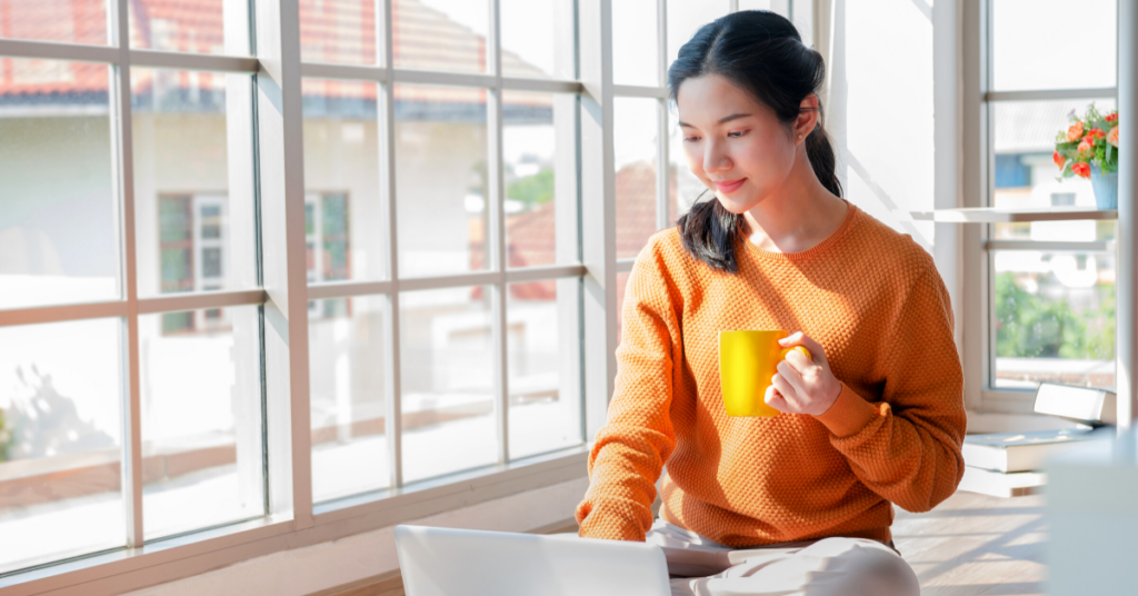 young asian woman on computer holding yellow coffee cup