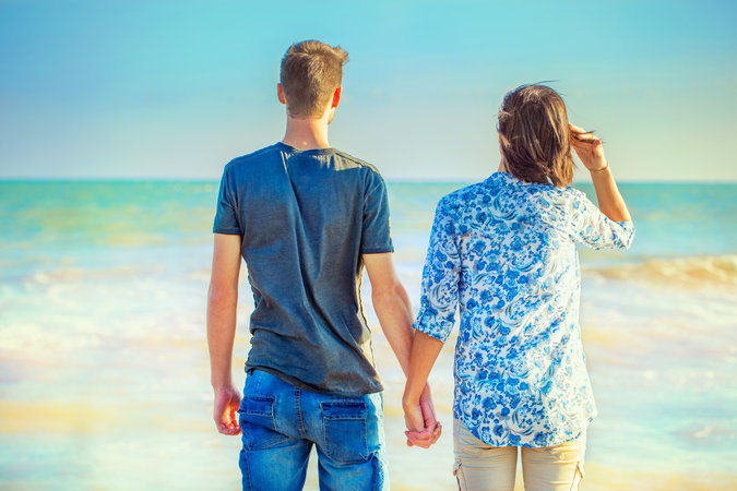 Young Couple Walking at the Beach While Holding Hands