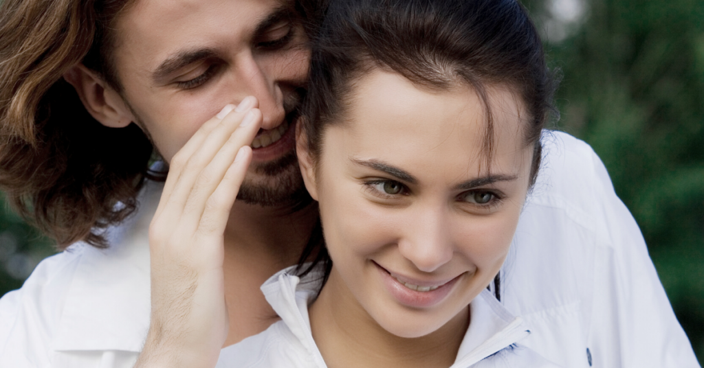 man whispering words of affirmation in wife's ear