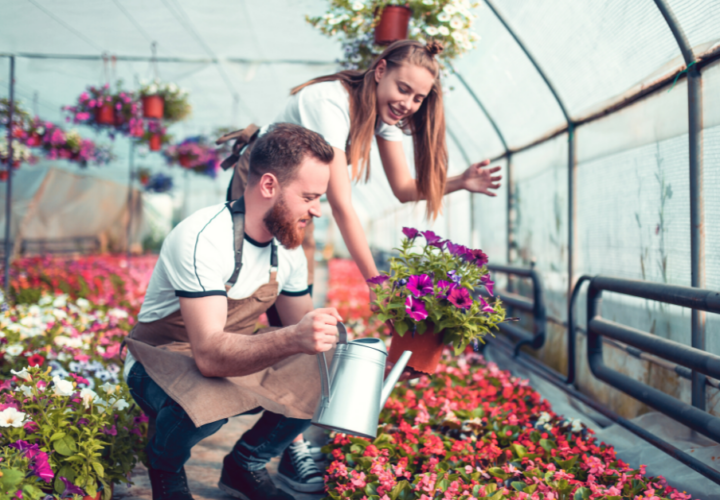 couple in greenhouse watering flowers